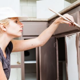 woman painting kitchen cabinets
